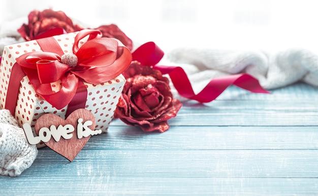 Композиция любви с праздничным подарком и декоративными элементами на деревянной поверхности крупным планом.