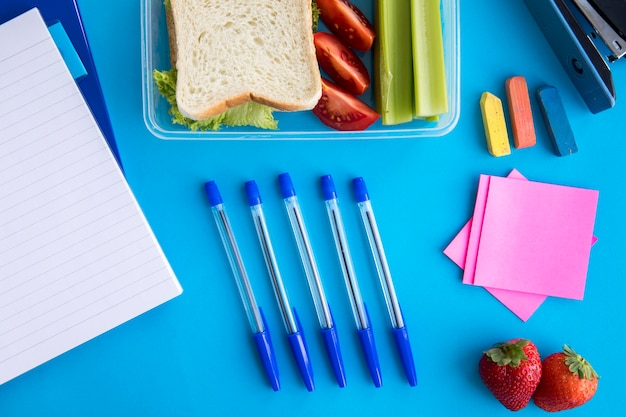 Composition of lunchbox and stationery on table