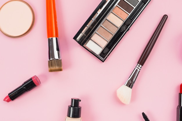 Composition of makeup and cosmetic beauty products laying on pink background