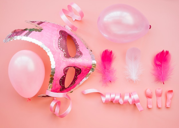 Composition of mask near balloons and feathers