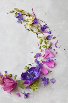 컴포지션은 발렌타인 데이, 결혼식 등을 위한 선물 또는 선물로 사용할 수 있습니다. 반달 형태로 회색 배경 위에 표현되는 꽃의 구성.