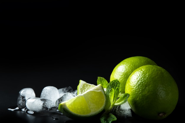 Composition of melting ice cubes with aromatic mint leaves and ripe green limes