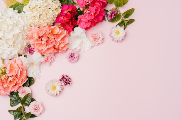 Composition of mixed flowers on pink background. top view, copy space.