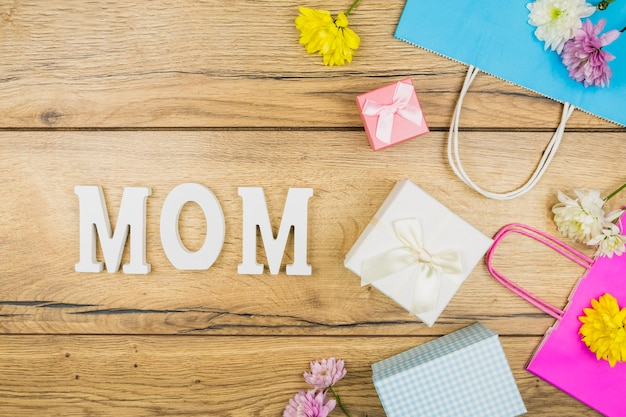 Composition of mom title near fresh flowers, present boxes and paper packets
