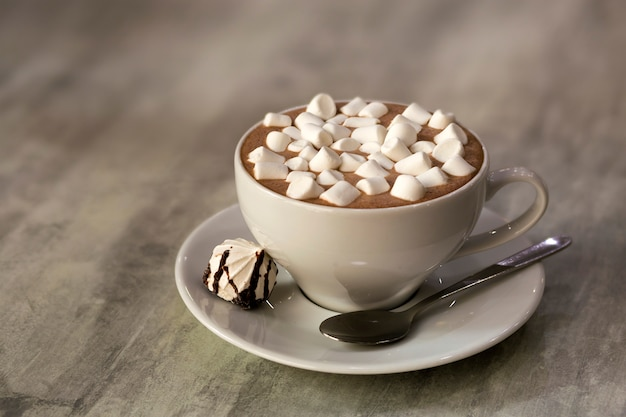 Composition of mug of coffee with marshmallows on porcelain plate on light background, top view.