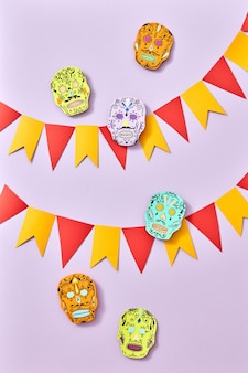 Composition of multicolored paper handcraft flags and skulls calaveras attribute of the mexican holiday of calaca on a purple background with space for text. halloween. flat lay