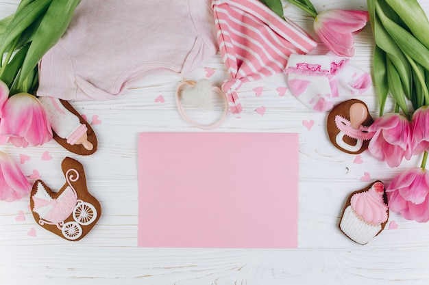 Composition for newborns on a wooden background with clothes, pink tulips and a cookies