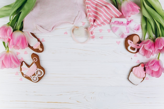 Composition for newborns on a wooden background with clothes, pink tulips, hearts.