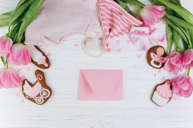 Composition for newborns on a wooden background with envelope, clothes and a cookies