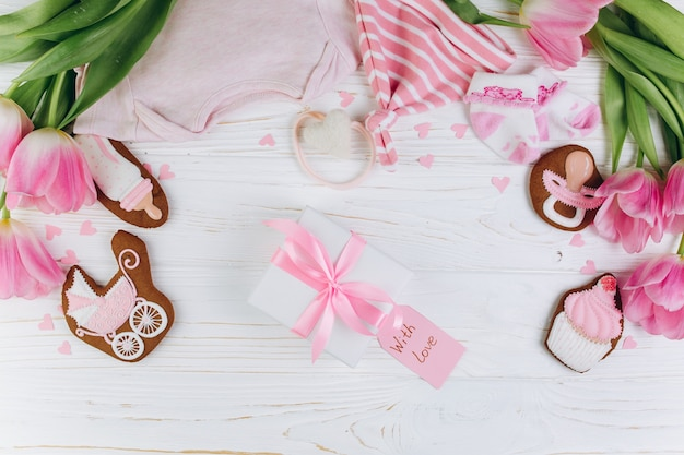 Composition for newborns on a wooden background with gift, clothes, pink tulips.