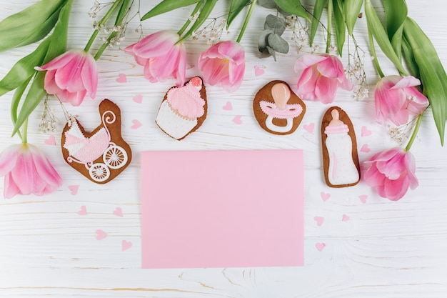Composition for newborns on a wooden background with pink tulips, hearts and a cookies