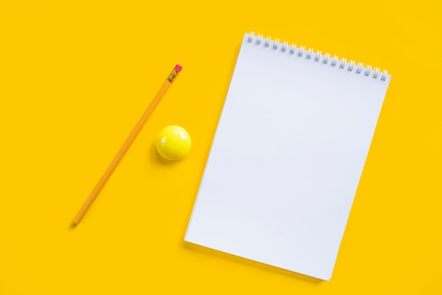 Composition of notebook pencil and yellow magnet