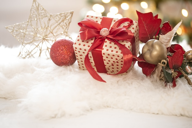 Композиция рождественского подарка и новогоднего украшения на светлом фоне копирует пространство.