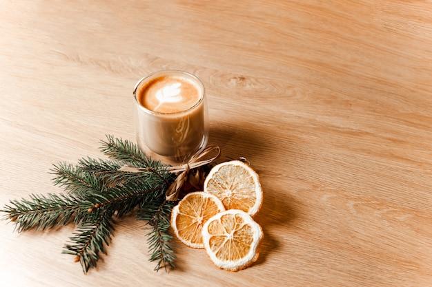 Состав чашки латте, кофейных зерен, сушеных апельсинов и еловой ветки