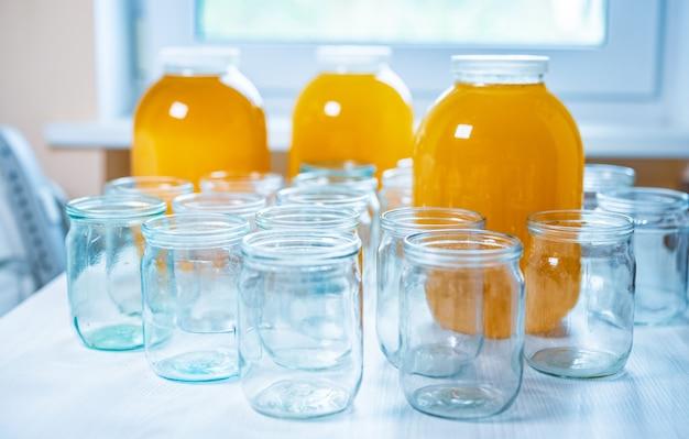 Композиция из большого количества банок и трех банок меда, стоящих на белом столе на фоне света