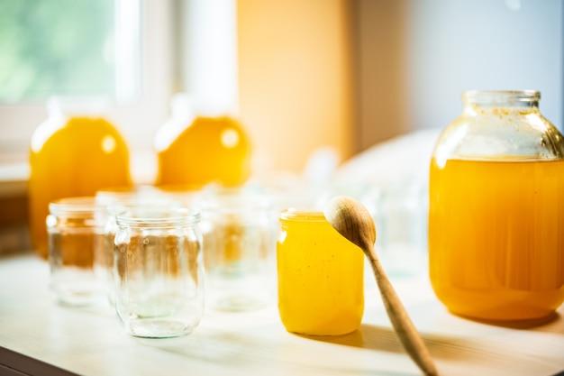 光を背景に白いテーブルの上に立っている多数の瓶と蜂蜜の3つの瓶の構成