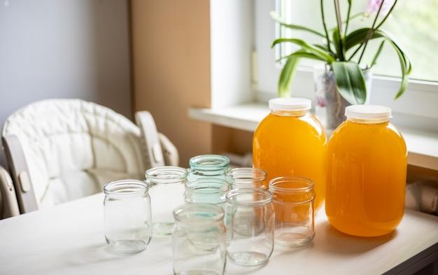Композиция из большого количества прозрачных пустых стеклянных банок и трех больших стеклянных прозрачных банок с желтым сладким медом, стоящих на большом белом столе на фоне яркого солнечного света.