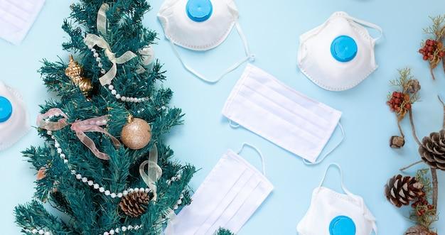Композиция из новогодней елки 2021 и медицинских масок на голубом фоне. концепция нового года во время коронавируса covid-19