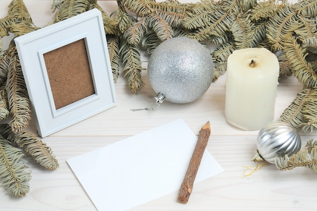 白い木の表面にクリスマスをテーマにしたフォトフレーム、紙、鉛筆の構成