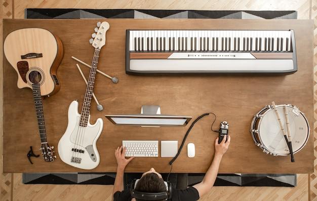 Композиция звукорежиссера, работающего на компьютере с наушниками и акустической гитарой, бас-гитарой, малым барабаном на коричневом столе.