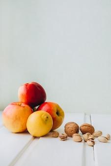 木製の白い背景にリンゴ、ピスタチオ、クルミの組成。