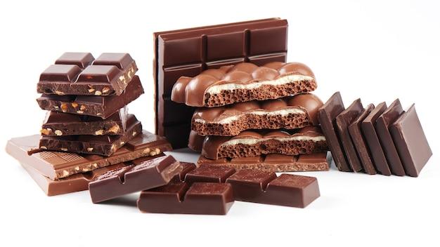 Композиция из плиток и кусочков разного молочного и темного пористого шоколада с орехами и кокосом на белом фоне крупным планом, вид сбоку