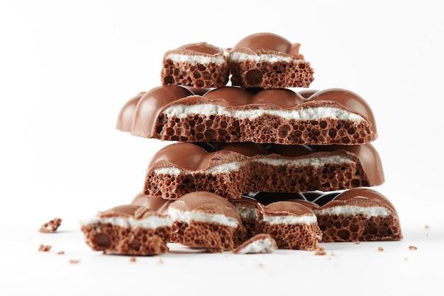 Композиция из плиток и кусочков пористого молочного шоколада с крупным планом слоя кокоса на белом фоне изолированы