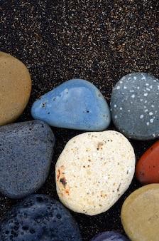 Композиция из красивых пляжных камней, окруженных волнами