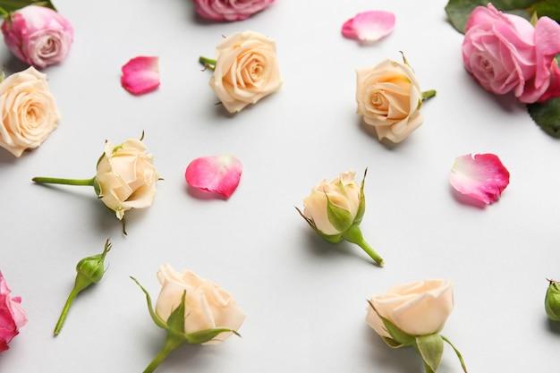 Композиция из красивых роз и лепестков на светлом столе