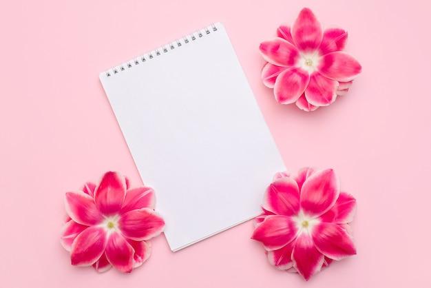 빈 종이 책상 나선형 노트의 구성은 밝은 분홍색 표면에 분홍색 꽃으로 장식합니다.