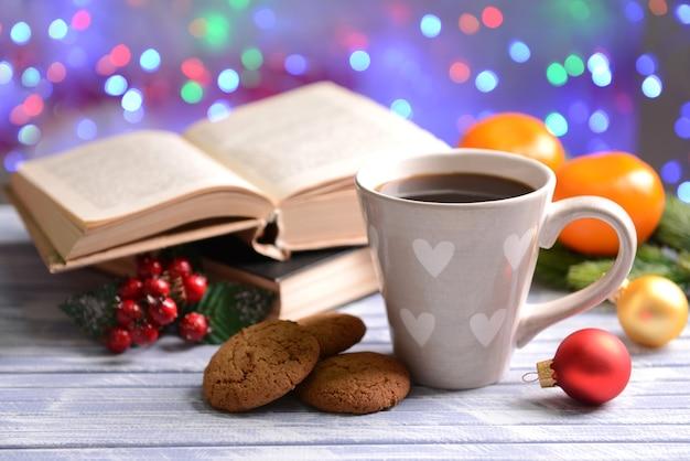 明るい背景のテーブルの上のコーヒーとクリスマスの装飾と本の構成