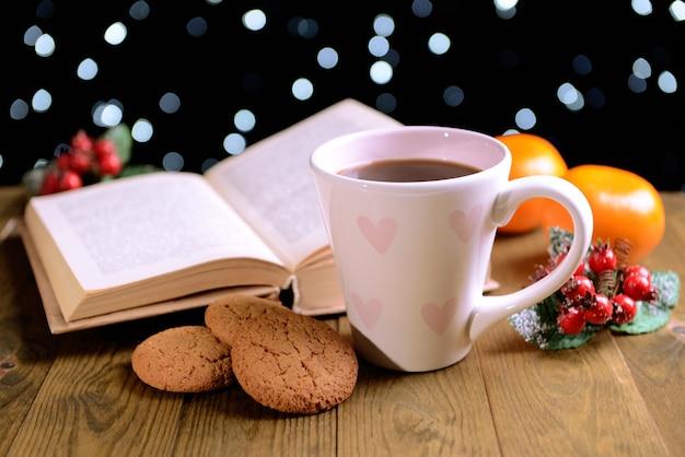 暗い背景の上のテーブルにコーヒーとクリスマスの装飾と本の構成