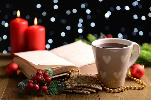 暗い背景の上のテーブルの上のコーヒーとクリスマスの装飾と本の構成