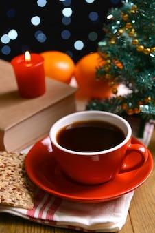 暗い壁のテーブルの上のコーヒーとクリスマスの装飾と本の構成