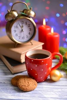 一杯のコーヒーとテーブルの上のクリスマスの装飾と本の構成