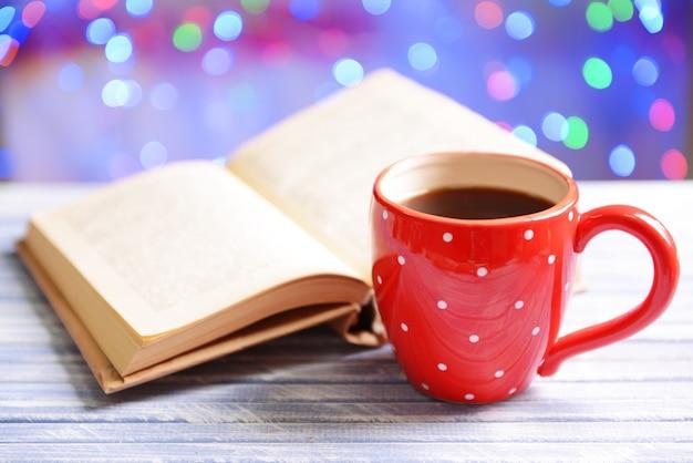 明るい背景のテーブルの上のコーヒーのカップと本の構成
