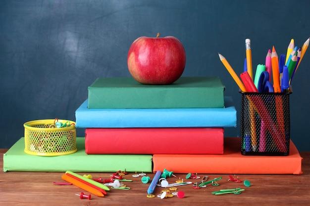 칠판 배경에 교사 책상에 책, 문구 및 사과의 구성