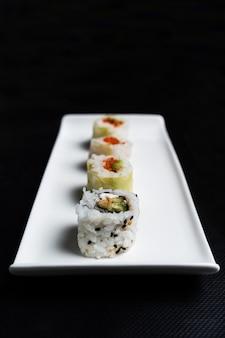 검은 배경에 흰색 세라믹 접시에 캘리포니아 스시 롤의 조성. 일본 요리는 수직 방향으로 가깝습니다.