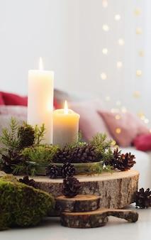 Композиция из свечей на белом столе на фоне дивана дома