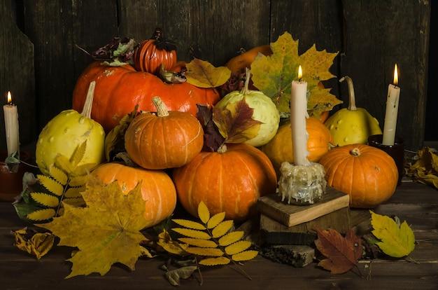 Композиция из свечей, тыкв и осенних листьев на старой деревянной поверхности