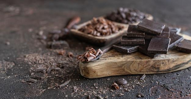 Композиция из кусочков шоколада, капель и чипсов фон с различными видами шоколада