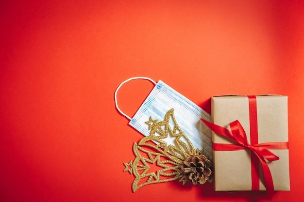Композиция рождественских украшений, подарочной коробки в ленте и защитной медицинской маски на красном фоне.