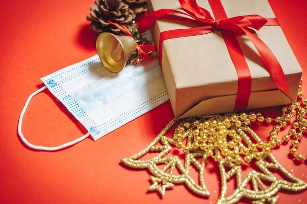 クリスマスの飾り、リボンのギフトボックス、モミの実、保護用医療用マスクの構成