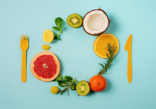 시안 색 배경에 감귤류 과일, 오렌지와 레몬, 코코넛, 키위의 구성