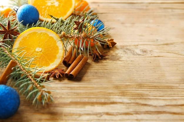 木製の背景に柑橘類、スパイス、針葉樹の枝の構成