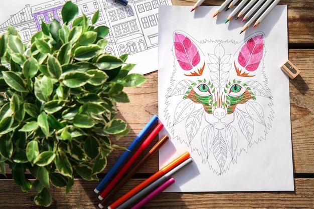 나무 테이블에 색칠 그림과 연필의 구성