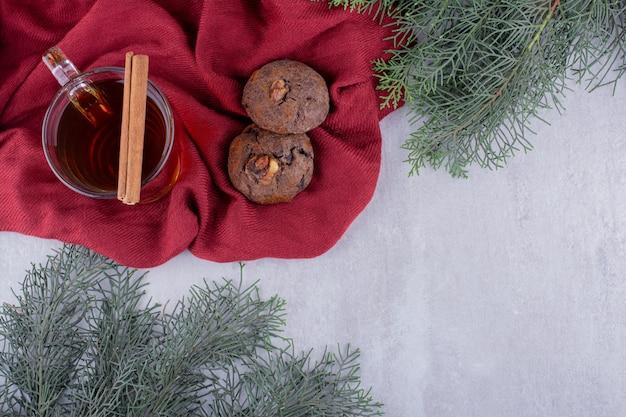 쿠키, 계 피 스틱 및 흰색 바탕에 차 한 잔의 구성.