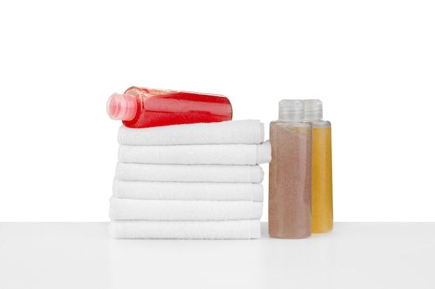白で隔離される化粧品のボトルとタオルの組成