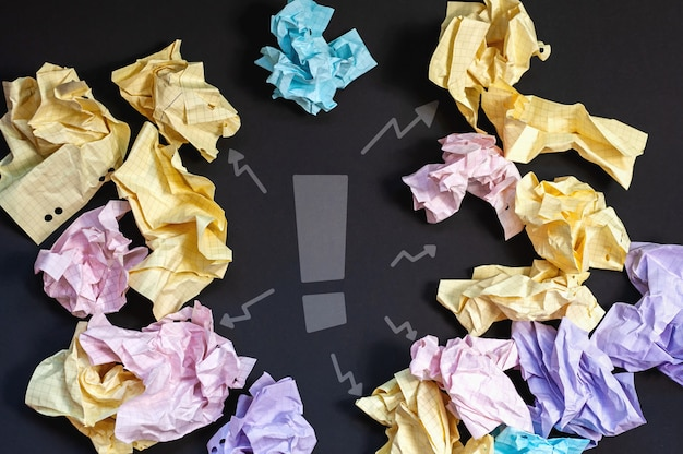 Композиция из мятой бумаги розового, желтого, синего и фиолетового цветов вокруг восклицательного знака