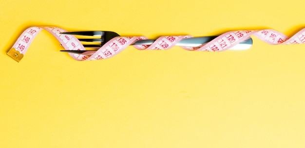 Композиция из свернутой обернутой измерительной ленты и вилки на желтом фоне. концепция избыточного веса.